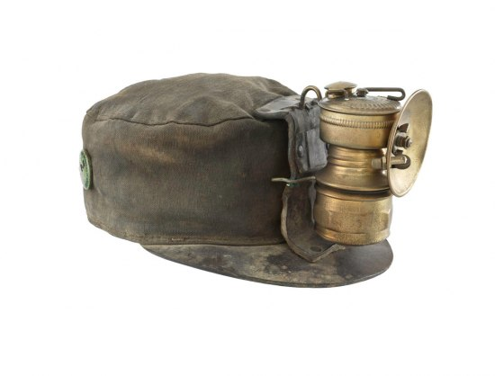 Photograph of a miner's hat from the 1930s. The cloth cap has a large lamp mounted on the brim.