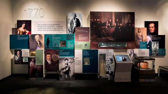 Photo of exhibit wall with portraits of people and text boxes with bios