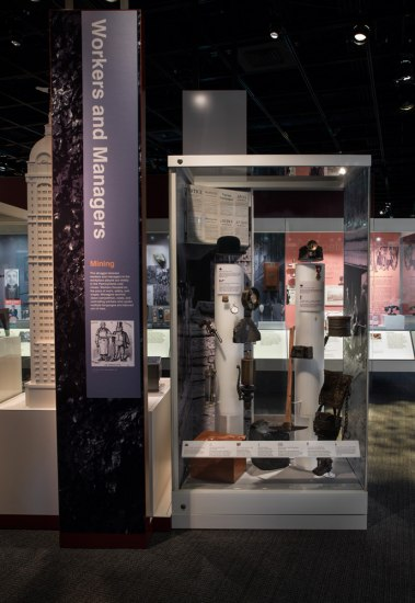 Photograph of the Workers and Managers section in the museum's American Enterprise exhibiiton. Varius artifacts representing miners and managers are arrayed side by side to contrsat the two groups.
