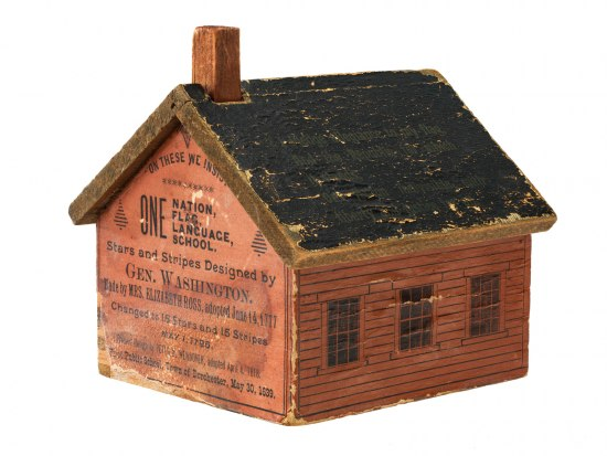 A small toy bank in the shape of a red schoolhouse decorated with text