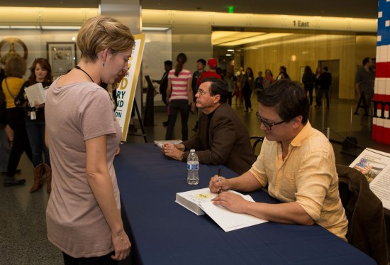 Two men signing books for young woman