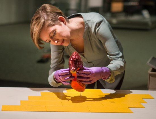 Color photo of a woman carefully handling a Ruby Slipper and placing it into a brace or mount for display.