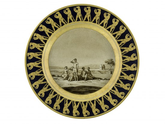 A black and gold decorative plate. A repeating pattern of a standing dog-like animal with its hands up rings the outside of the plate. There is a picture in the center of naked or half-naked people sitting outside on a sunny day. One is looking into the distance.