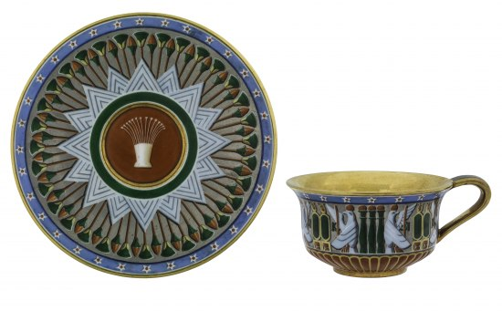 A cup and saucer. There are geometric patterns on both with shades of blue, green, and red.  On the cup is an eagle with a sun on its head and the plate has a lotus decoration.