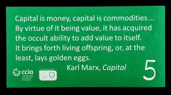 "A rectangular piece of paper currency. It has a black border and is kelly green with a quote from Karl Marx on it in white lettering. There is a ""5"" and several logos in the lefthand corner."