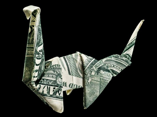 A one dollar bill folded into the shape of a dinosaur, specifically one of the plant-eating ones with a long neck.