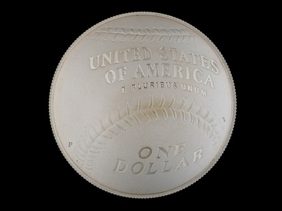 """A round silver coin that has a baseball design and says """"United States of America E Pluribus Unum / One dollar"""" on it. Its sides are ridged."""