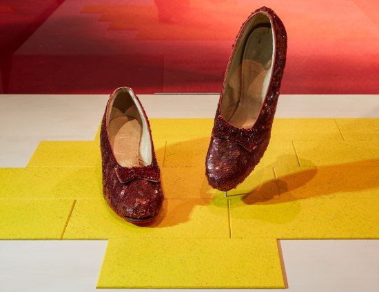 Photo of the Ruby Slippers on a yellow background.