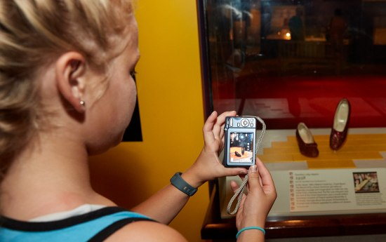 Girl with blonde hair takes a photo of the Ruby Slippers in a display case. The image can be seen on the screen of her camera.