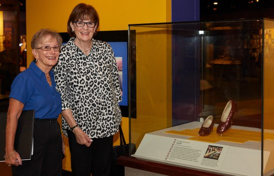 Two women pose with big smiles near the Ruby Slippers case in the museum