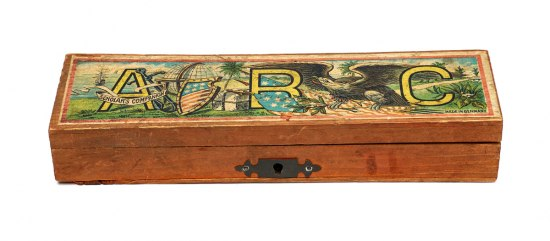 Thin wooden pencil box. The lid is decorated with cartoon illustrations, including a bald eagle, an American flag, a globe, and a ship at sea. The letters A, B, and C are prominently displayed in the background. The lid's bottom corner has the text: Made