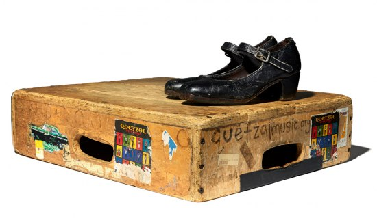 Photograph of a pair of black dancing shoe, The shoes sit on top of a plywood stomp box, called a tarima. The box is well-worn and decorated with stickers.