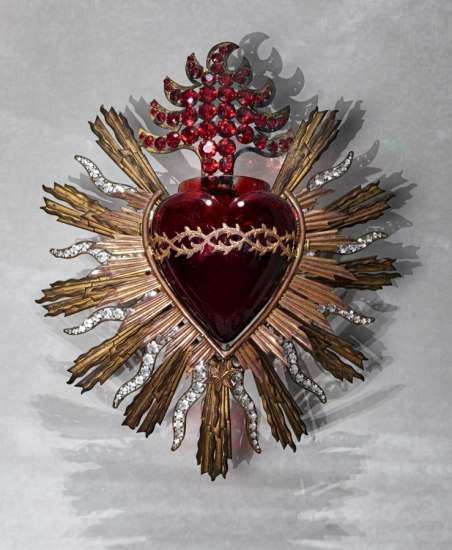 A glass heart with an elaborate metal design