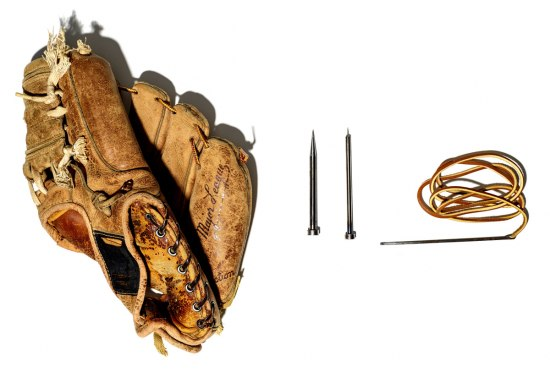 """Photograph of Ernie Martinez's re-stitched baseball glove and repair tools. The well-worn leather glove shows signs of repair. """"Major League"""" is inscribed on the palm. Next to the glove sit lace and two needles."""