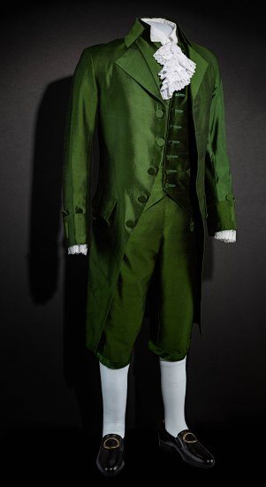 A green suit, consisting of a coat, vest, and breeches. The material has a sheen to it. The suit is complemented by white socks, black buckle shoes, and the ruffles of white shirt peeking out from beneath.