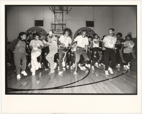 In a black and white photograph, Jackie Joyner-Kersee stands in the middle of a line of adults facing the camera dancing joyously. They are in what appears to be a high school and those in the photograph are wearing athleticwear