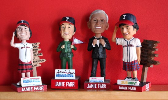 "Four ""bobblehead"" plastic characters, all smiling and wearing different baseball uniforms and accessories."