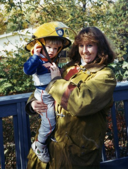 A young woman in firefighting gear holds a toddler wearing a large firefighting hat.