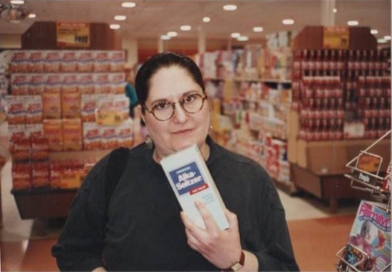 A woman with dark hair and glasses stands in a supermarket and holds a box of alka seltzer up to the camera