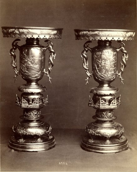 Two large vases with ornate metal work and designs. They are multi-level.