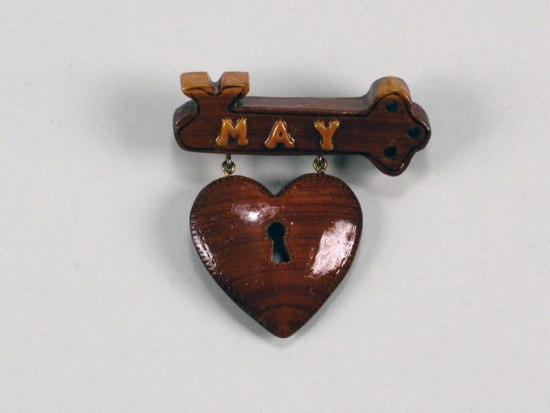 "Hand-carved pin with text ""May"" and small heart, made of wood"