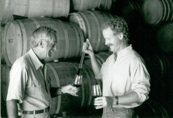 Black and white photo of two men in a wine cellar with barrels in background. One man, with a mustache, pours red wine into the other's glass. They both smile.