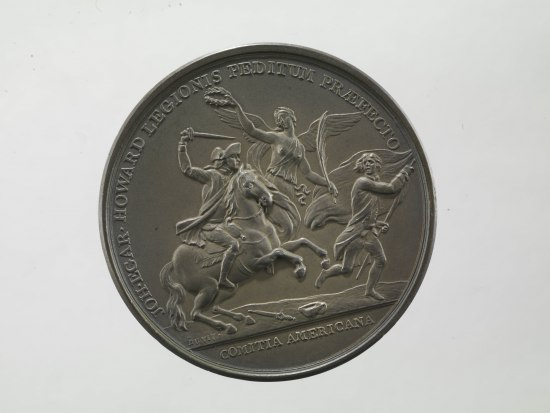 Coin with a dramatic scene. A man on a horse raises a sword. Beside him, a man runs with a flag flapping in the wind. In center, a winged female figure holds a wreath above the head of the man with the sword.