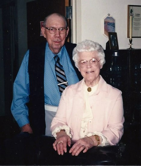 A photograph of an elderly couple. The woman wears a cardigan and a blouse and smiles, standing in from of the man, who has a shirt and tie on.