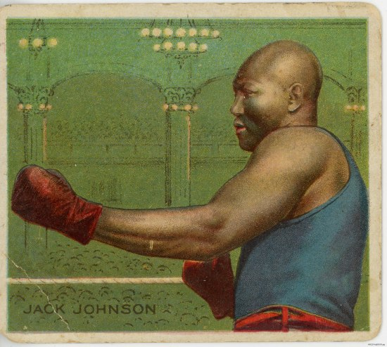A playing card on which a man wearing boxing clubs in a fighting stance stands against a green background made to look like a large hall with many seated people. He is identified as Jack Johnson by text in the corner.