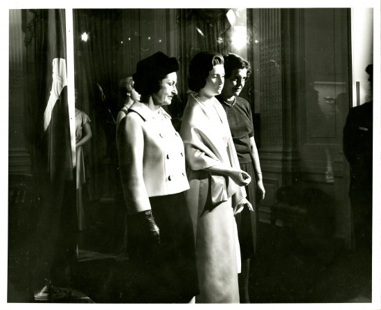 Black and white photo of Lady Bird Johnson in pea coat-cut blazer, gloves, and skirt, standing beside a mannequin wearing inaugural gown, with draped, silky fabric.