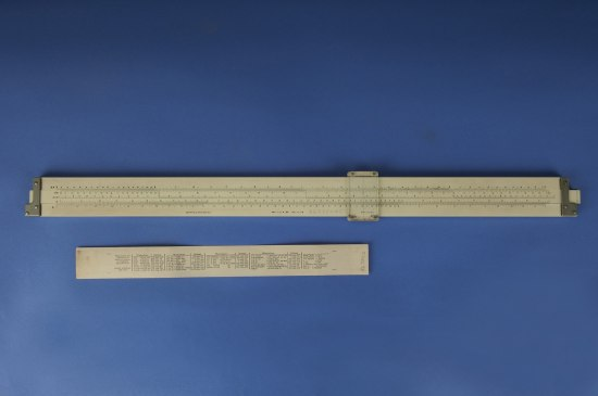 Two stick rulers lying on a blue background. One has markings and numbers on it with a clear slider and the other has equivalents typed on it in very small print.