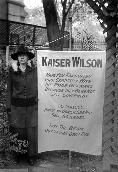 Woman wearing a hat stands next to a large cloth sign