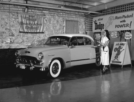 Photograph of an advertising display featuring a 1953 Dodge and woman gesturing towards the car and opening the driver's door.