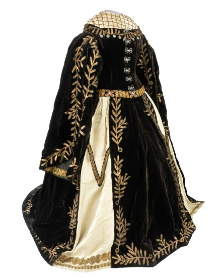 An old, ornate black gown with gold leaves and vines stitched along the hems and embroidery on the waist and collar. It has long, full sleeves and the skirt is slashed to show a cream underlayer with gold detailing.
