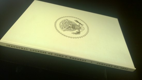 A thin, cream colored book with the presidential seal in gold on the cover