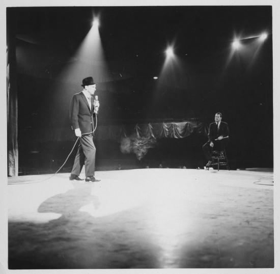 Black and white photograph of Frank Sinatra on stage under a spotlight, holding microphone in left hand