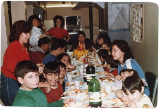 A long table with bottles of soda and a paper turkey in the middle sits in a kitchen or basement space. Young people sit around the table, adults stand behind them. Some laugh, some smile, some eat.