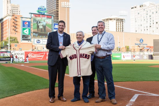 """Photo of four men on a baseball field. One holds a """"Jamie Farr"""" baseball jersey."""