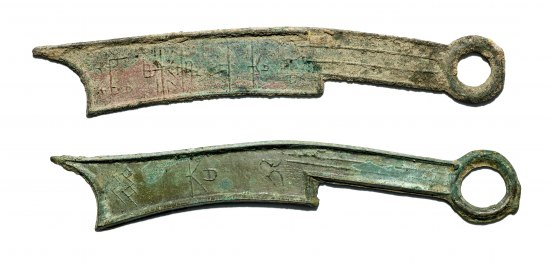 """Two pieces of metal shaped roughly like machetes with loops at the end of the """"handles."""" They are greenish in color though one has some dull copper coloring."""