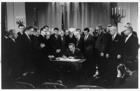 Lyndon Johnson, seated, signs the Fair Housing Act surrounded by onlookers