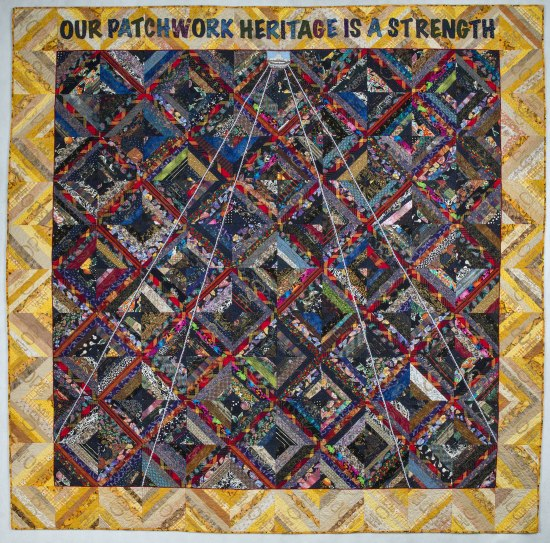 A quilt that is a patchwork with a variety of colored diamonds and a border with zigzag pattern