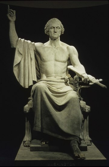 A stone statue of a seated George Washington in a classical style toga. He is bare to his lap and holds out a sword in a scabbard with his other hand raised, index finger aloft