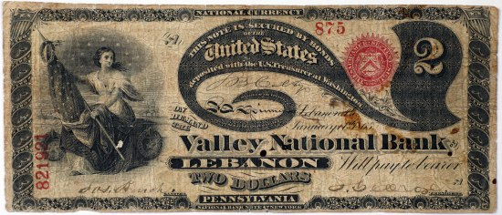 A rectangular piece of currency with worn edges. It has a decorative border and within it is a seated woman cradling a starry flag. In various typefaces there is different information on the rest of the currency; a great, leaf-like flourish extends across the page.