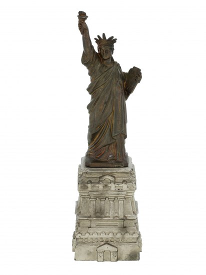 A bronze Statue of Liberty sits atop a replica base made from a white material. It shows its age with black marks on the white part.