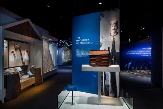 A view of an exhibit. Much of it is dark but some of it is spot-lit. There are signs and artifacts on pedestals.
