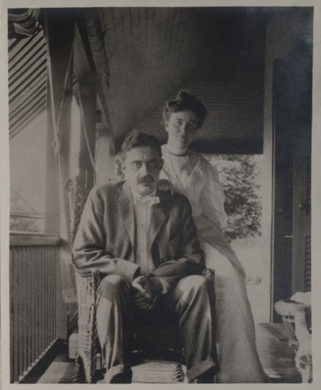 A black and white photograph showing a man and a woman on a porch. He is seated and she is perched on the back of the chair. It is light outside.