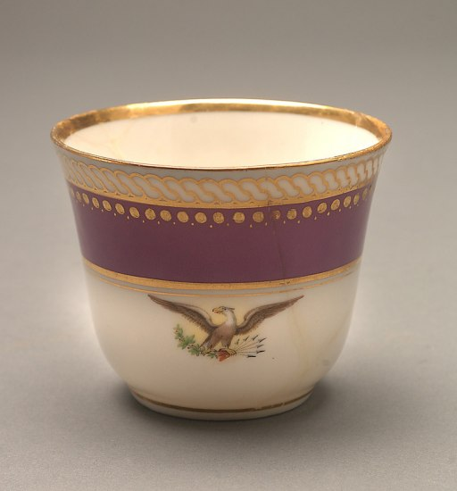 A handle-less white cup with a red band, gold embellishments, and a prominent eagle design