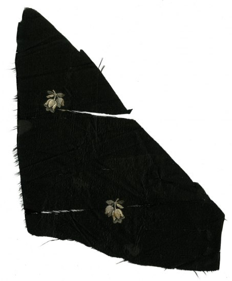 Scrap of black cloth with white flower designs