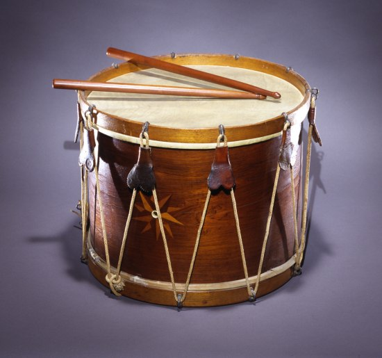 Wooden drum with two drumsticks, decorated with black crepe.