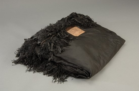 A bundle of black crepe with tassels. A printed note of identification sits on top.